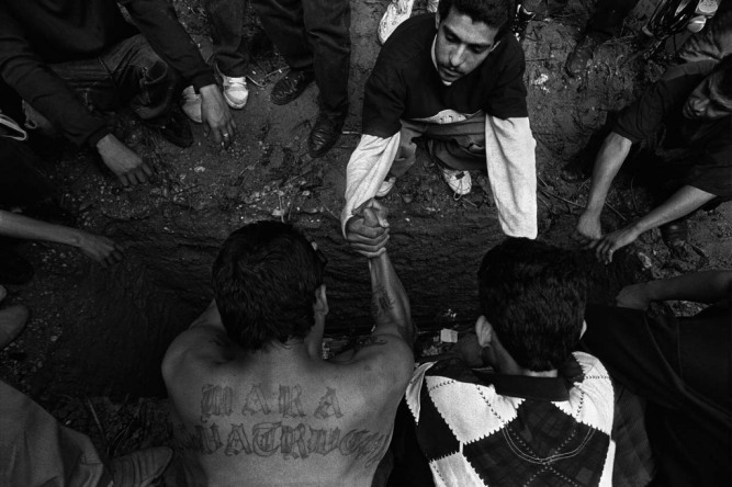 San Salvador, El Salvador 1996 Gang members make a pact of revenge over the grave of a slain leader. Photos by Donna De Cesare. From the book Unsettled/Desasosiego © 2013 by The University of Texas Press.
