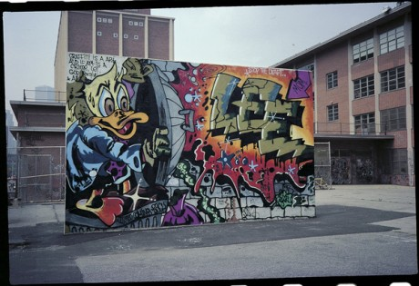 ç=Howard the Duck Handball Court photograph by Charlie Ahearn. A photograph of friend Lee Quiñones' massive 1988 handball court mural, created 10 years earlier and since destroyed, at Corlears Junior High School on Manhattan's Lower East Side.