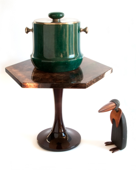 Artwork: An Aldo Tura ice bucket on an Aldo Tura presentation table. Both covered in dyed parchment (goatskin). Aldo Tura's parchment dyes are unmatched today. The Kay Bogensen penguin has an articulated neck and the grain of the wood is incorporated into the sleek form of the bird.